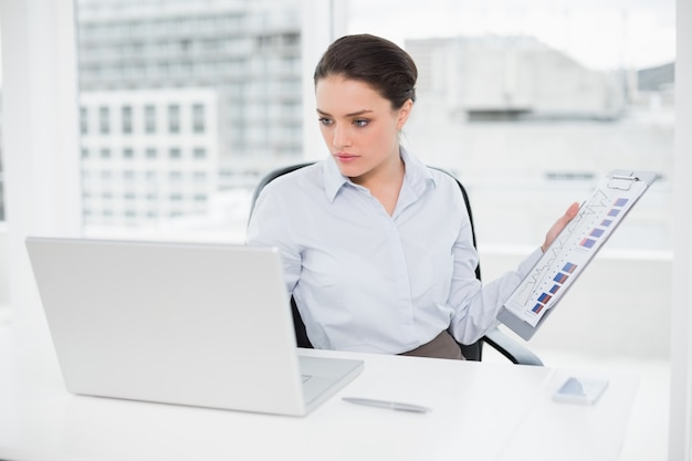 Businesswoman with graphs and laptop in office