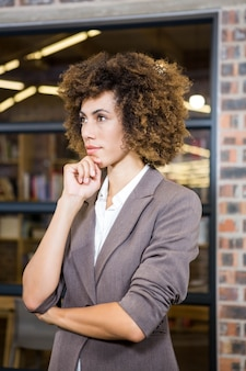 Businesswoman with hand on chin in office