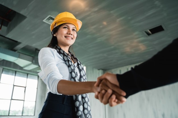 Businesswoman with hardhat shaking hands