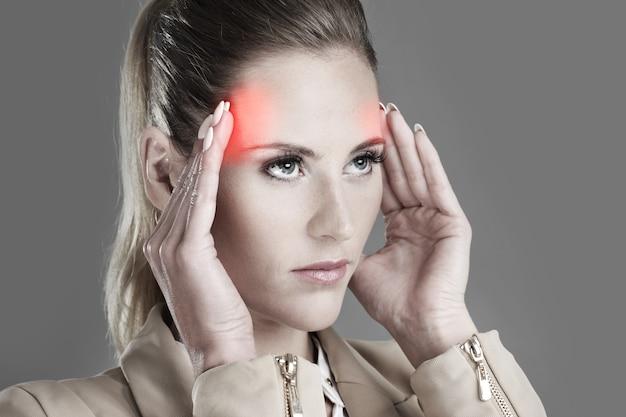 Бизнесвумен с головной болью на сером фоне