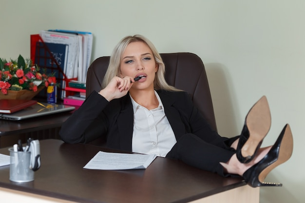 Businesswoman with her foot on the desk