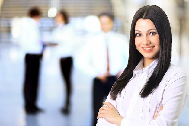 그녀의 직원, 현대 밝은 사무실 실내에서 백그라운드에서 사람들 그룹과 사업가