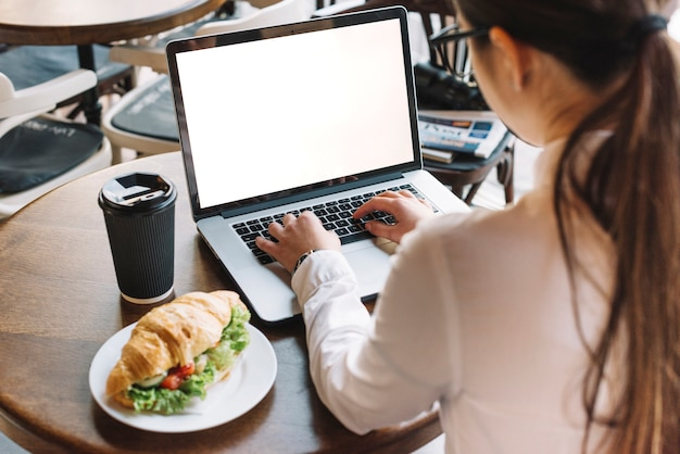 Businesswoman with laptop in coffee shop