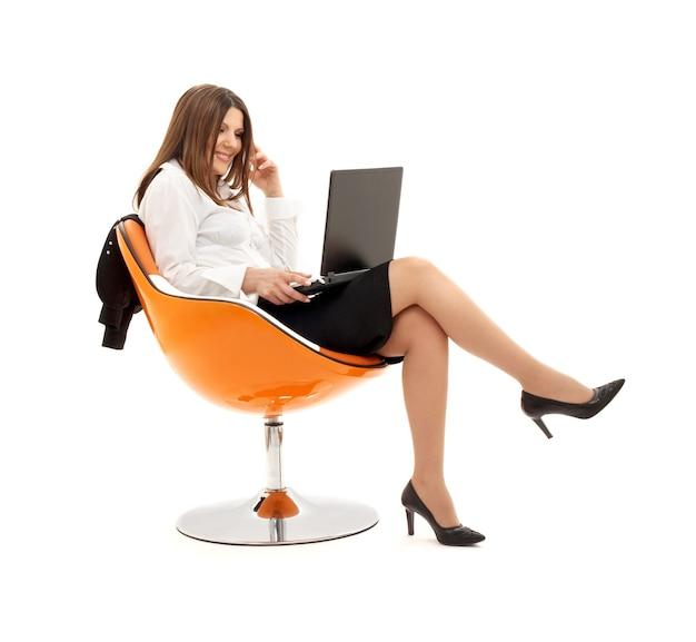 Деловая женщина с ноутбуком в оранжевом кресле над белой