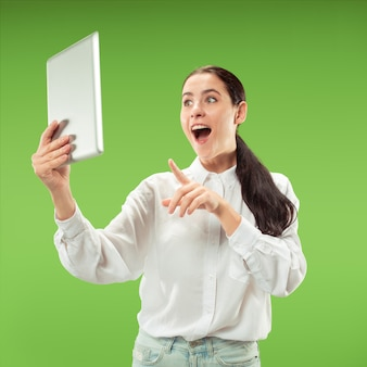 Businesswoman with laptop. love to computer concept. attractive female half-length portrait, trendy green  wall. young emotional pretty woman. human emotions, facial expression