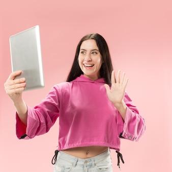 노트북과 사업가입니다. 컴퓨터 개념에 사랑. 매력적인 여성 절반 길이 전면 초상화, 트렌디 한 핑크 backgroud