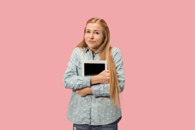 ラップトップを持つ実業家。コンピュータの概念が大好きです。魅力的な女性のハーフレングスのフロントポートレート、トレンディなピンクのスタジオの背景。若い感情的な女性。