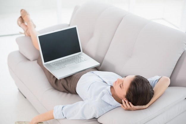 Businesswoman with laptop lying on sofa at home