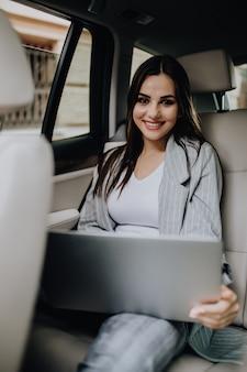 車の後部座席で電話を受けるラップトップを持つ実業家。車でオフィスに旅行中に働く女性起業家。