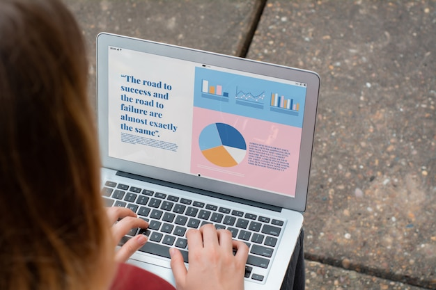 Businesswoman with laptop showing statistics about company growth
