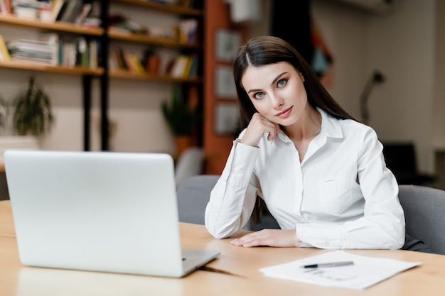 Businesswoman with laptop works at desk with documents