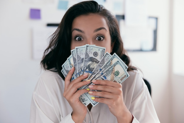 Businesswoman with long brown hair in formal wear white shirt holding lots of dollar banknotes