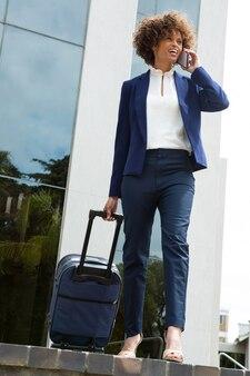 オフィスビルの近くで携帯電話で話している荷物袋を持つ実業家