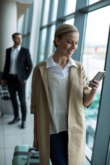 Businesswoman with luggage using mobile phone