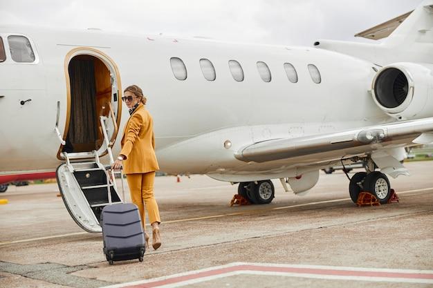プライベート飛行機のジェット機に歩いて荷物を持つ実業家。はしご付きの現代の旅客機。女性の背面図はフォーマルなスーツと眼鏡を着用します。民間航空。空の旅とビジネスの概念