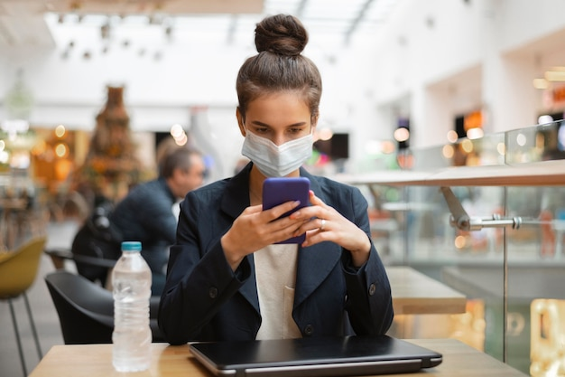 Businesswoman with medical mask checking her phone