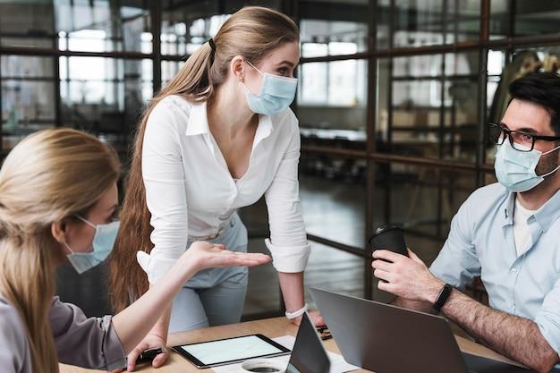 彼女の同僚との専門家会議を開催する医療マスクを持つ実業家