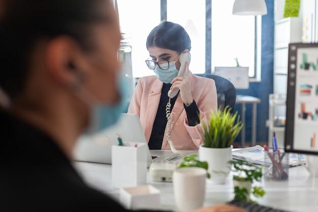 コロナウイルスに対する医療保護フェイスマスクを持つ実業家
