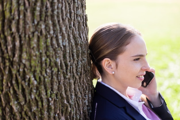 Businesswoman with mobile phone resting on a tree