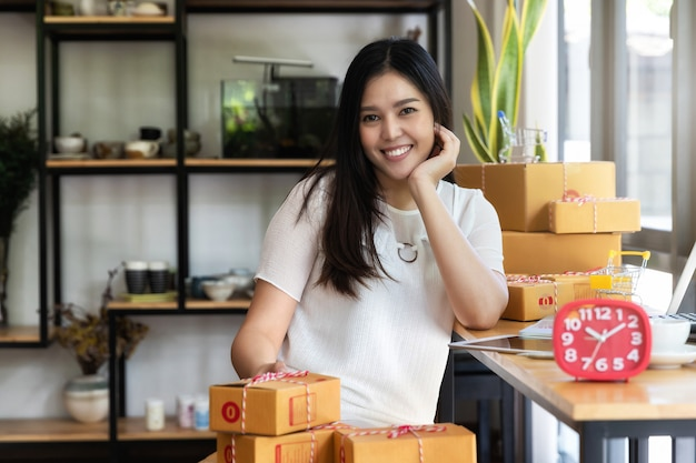 Businesswoman with online sales and parcel shipping in her home office.