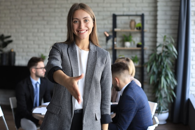 Businesswoman with an open hand ready for handshake in office.