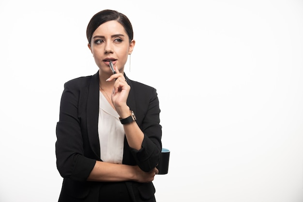 Businesswoman with pencil and cup on white wall.