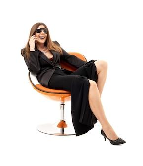 Деловая женщина с телефоном в оранжевом кресле над белой