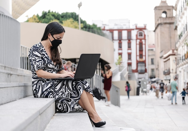 Businesswoman with a protective mask working with her laptop outside
