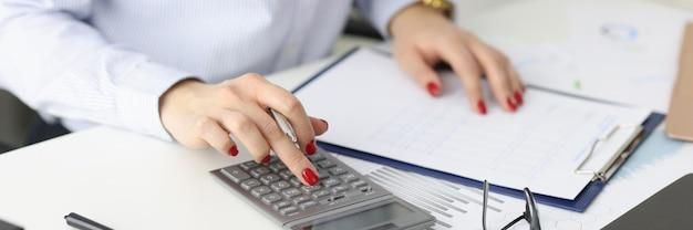 Деловая женщина с красным маникюром, рассчитывающая на калькулятор в вычислении крупного плана офиса