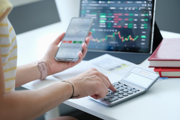 Businesswoman with smartphone calculator and laptop calculates exchange changes of stock market