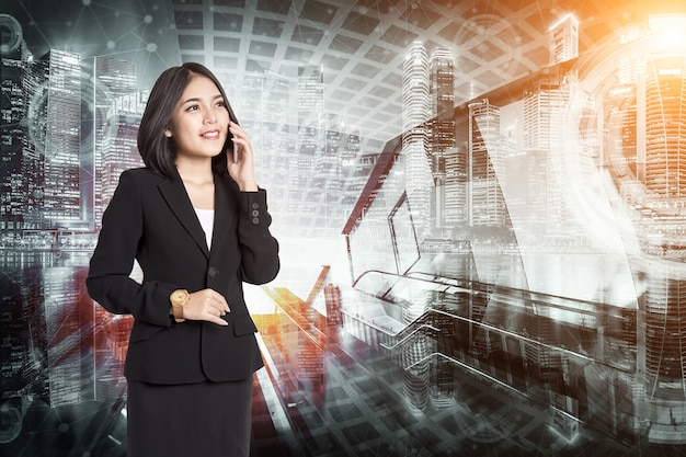 Businesswoman with smartphone talking over city background