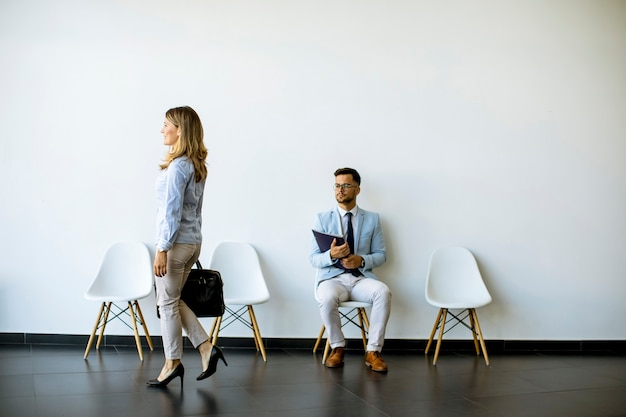Businesswoman with suitcase passing by young man sitting at chair in the waiting room with a folder in hand before an interview