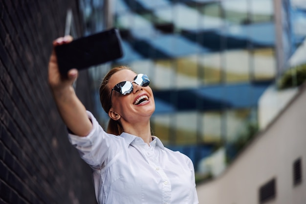 Businesswoman with sunglasses standing outside and taking selfie. business center exterior.