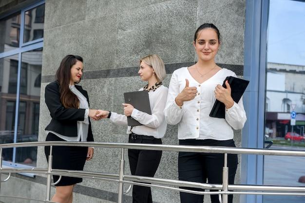 Деловая женщина с планшетом стоит перед своими коллегами, которые обсуждают некоторую информацию