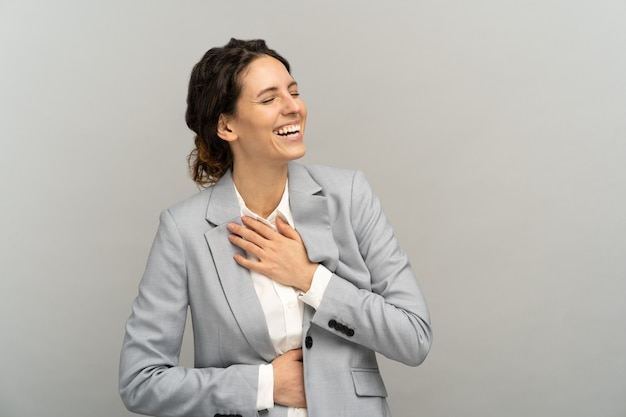 Businesswoman with toothy smile laughing loud at joke holding her belly and chest having fun. studio