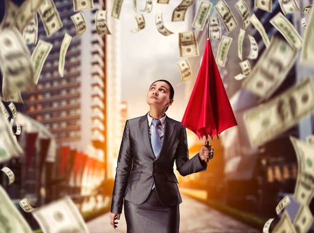 Businesswoman with umbrella in money rain