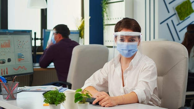 Businesswoman with visor and mask talking in front of camera having video call with partners. pov of manager speaking with remotely team during online conference while colleagues working in background