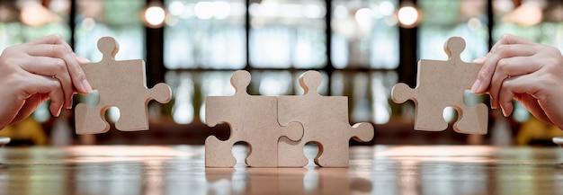 Деловая женщина с деревянной головоломкой и головоломкой для концепции успеха бизнеса. символ совместной работы и достижения.