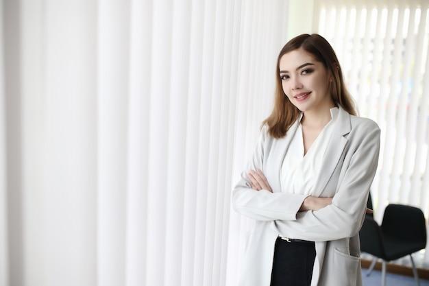 Предприниматель, женщина стоит возле окна офиса