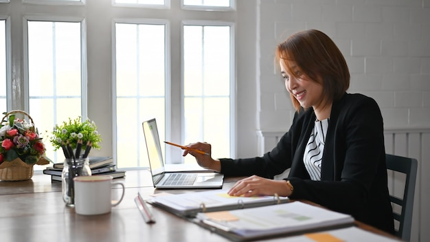 Businesswoman working analysis on laptop computer, business finances and accounting concept.