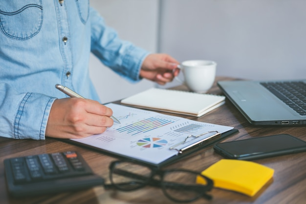 Businesswoman working and analyzing financial graph with documents on desk office.