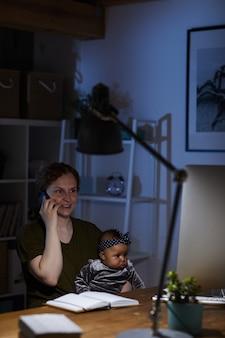 Деловая женщина, работающая дома до ночи, разговаривает по мобильному телефону, сидя за столом со своей маленькой дочерью