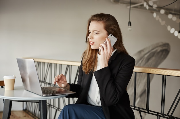 Businesswoman working in cafe, answer calls and looking at laptop