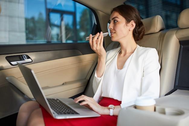 Businesswoman working in car
