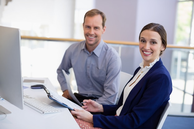 Businesswoman working at desk with colleague