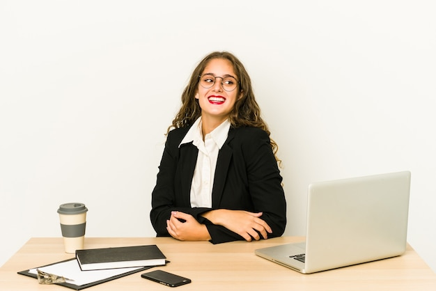Businesswoman working on her desktop looks aside smiling