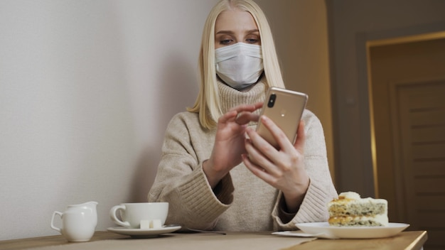 Businesswoman working on a laptop in a cafe in a medical mask, removes. removal of quarantine measures.