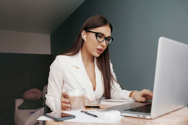 Businesswoman working on laptop computer sitting at home managing her business via home office during coronavirus or covid-19 quarantine