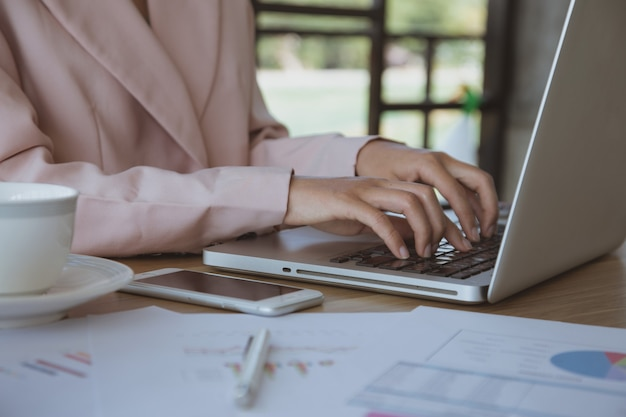 Businesswoman working on laptop in her workstation.black blank screen smartphone, potted plant, pencil, notes, earphone on wooden desk. close up