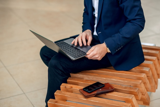A businesswoman working on a laptop sitting on a bench